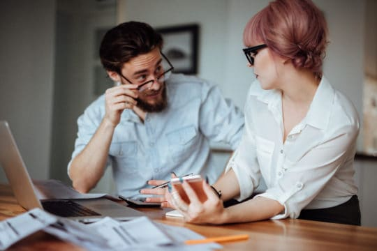 Millennials are saving for retirement. Photographed is a young couple budgeting their finances.