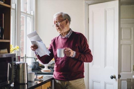 Senior man holding bill in hand. One individual heading toward a senior debt crisis.