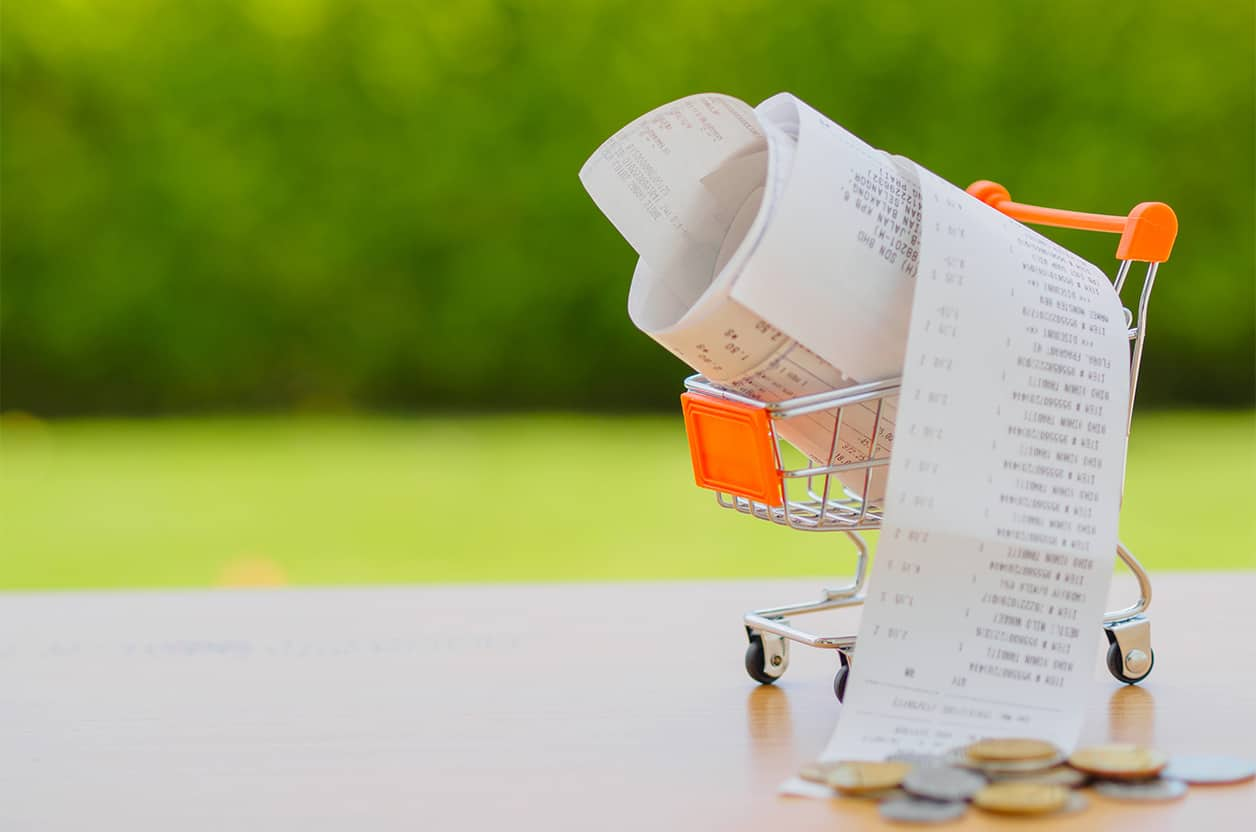 Shopping cart with receipt with coins on wooden table. Sell-by dates cost you money on your grocery bill.