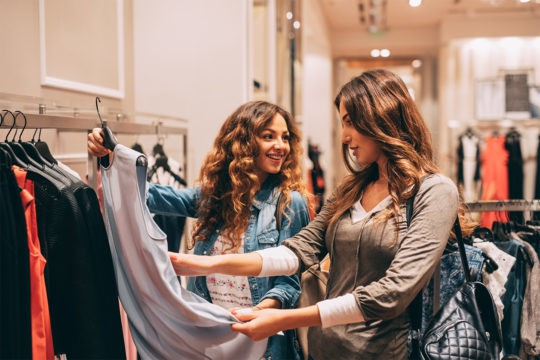 Millennials and retirement savings: They'd rather spend now on clothes than save for the future. Photo of two friends shopping in a clothing store.