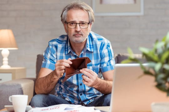 Worried man showing empty wallet. Bankruptcy concept. Bankruptcy among Americans, 65 and older, is three times higher than what it was in 1991.