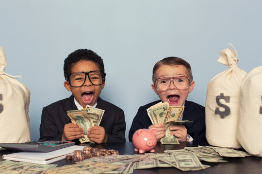 Young business children make faces holding lots of money. Teach your kids about money.