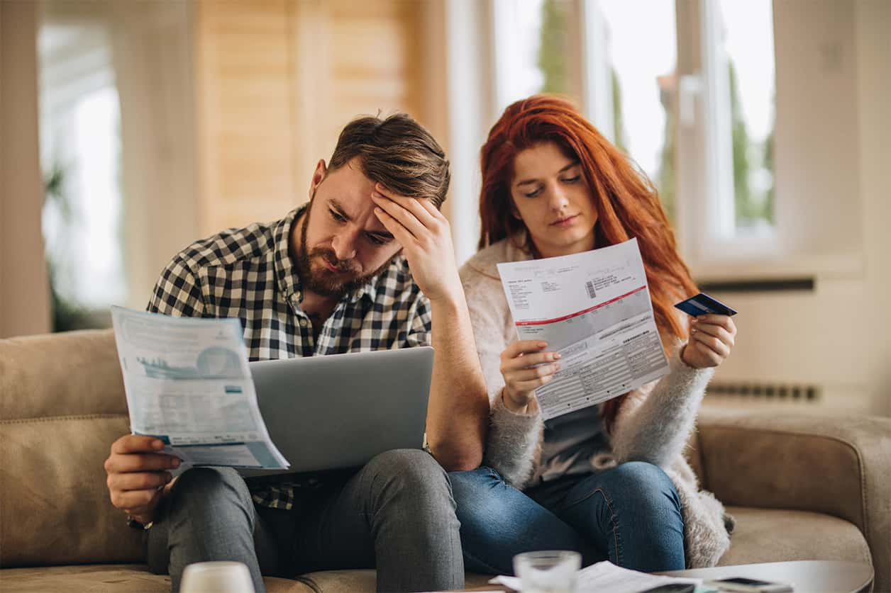 Worried couple feeling frustrated while checking late payments on credit report.
