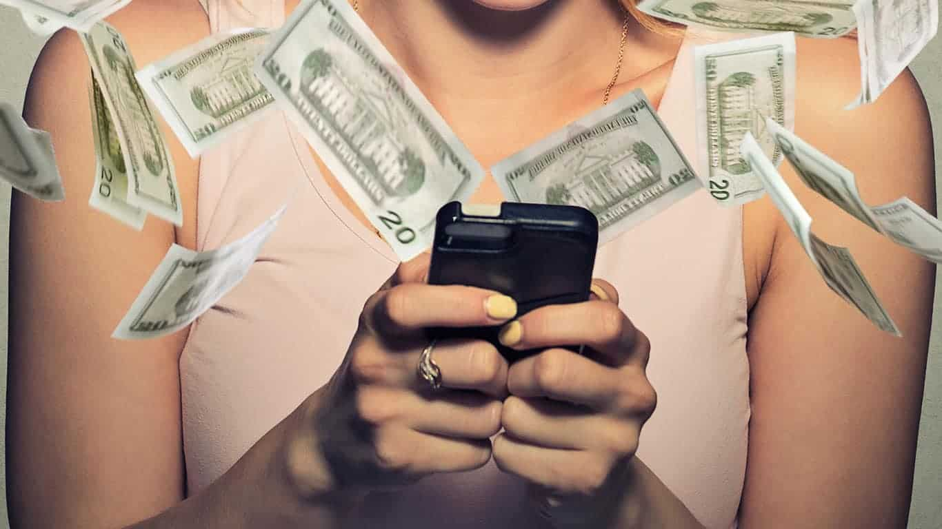 Woman using smartphone with dollar bills flying from screen