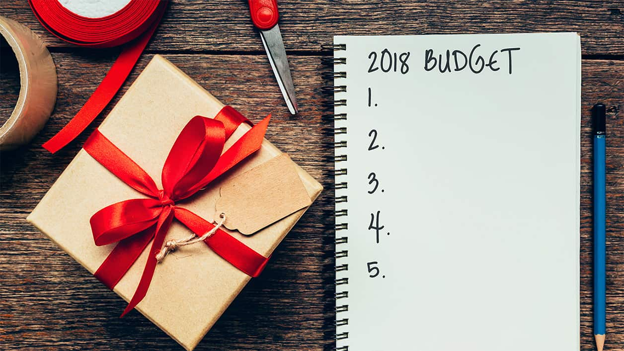 throw a holiday party on a budget. 2018 Budget text on notebook paper with gift box