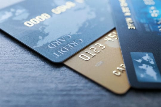 Different credit cards on table, closeup. Cash or credit card? More Americans prefer paying with cash on smaller purchases.