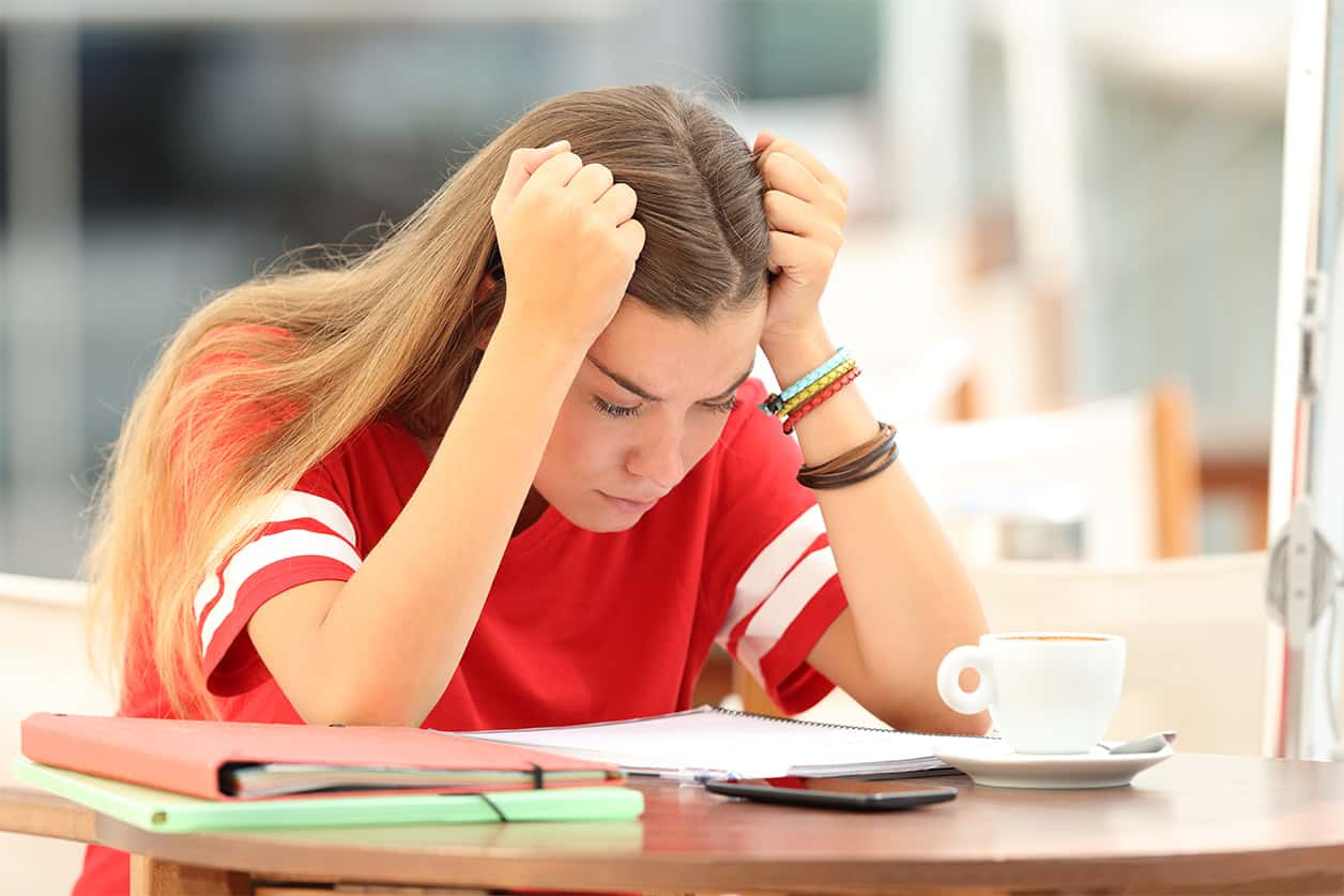 cost of college textbooks stress students out. Frustrated student trying to understand notes in a bar