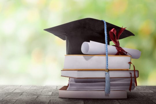 The best college degrees to get a job: Graduation hat with degree paper on a stack of book against blurred background.