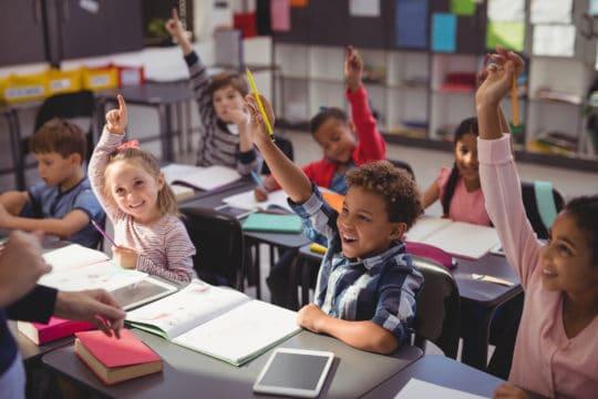 Schoolkids raising their hands in classroom at school
