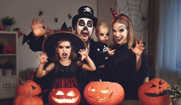 A budget friendly Halloween. Happy family — mother, father, and children in costumes and makeup on Halloween.
