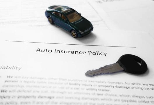 Auto insurance policy with key and miniature car