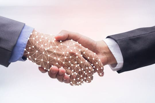 Close up business man handshake with business artificial intelligence (AI) on motion blur background for future technology concept