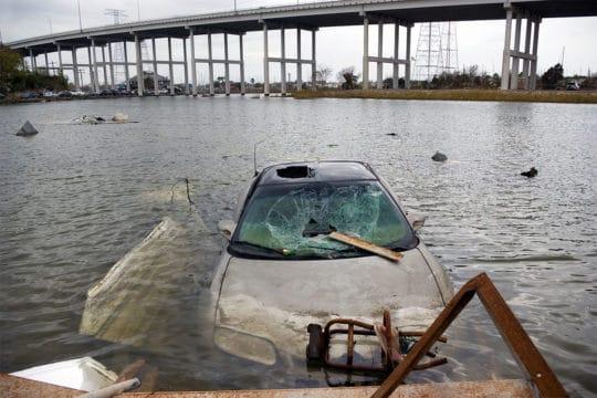A flood damage car sits hopelessly submerged near an overpass
