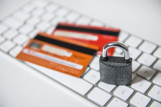 High angle view of a padlock with credit cards over computer keyboard. Depicting how to recover from identity theft.
