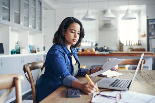 woman using a laptop and going through paperwork.