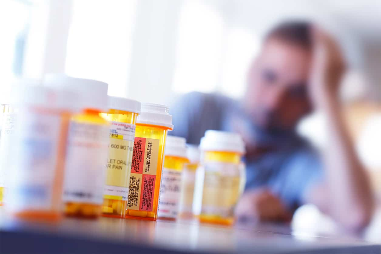 A large group of prescription medication bottles sit on a table in front of a distraught man.