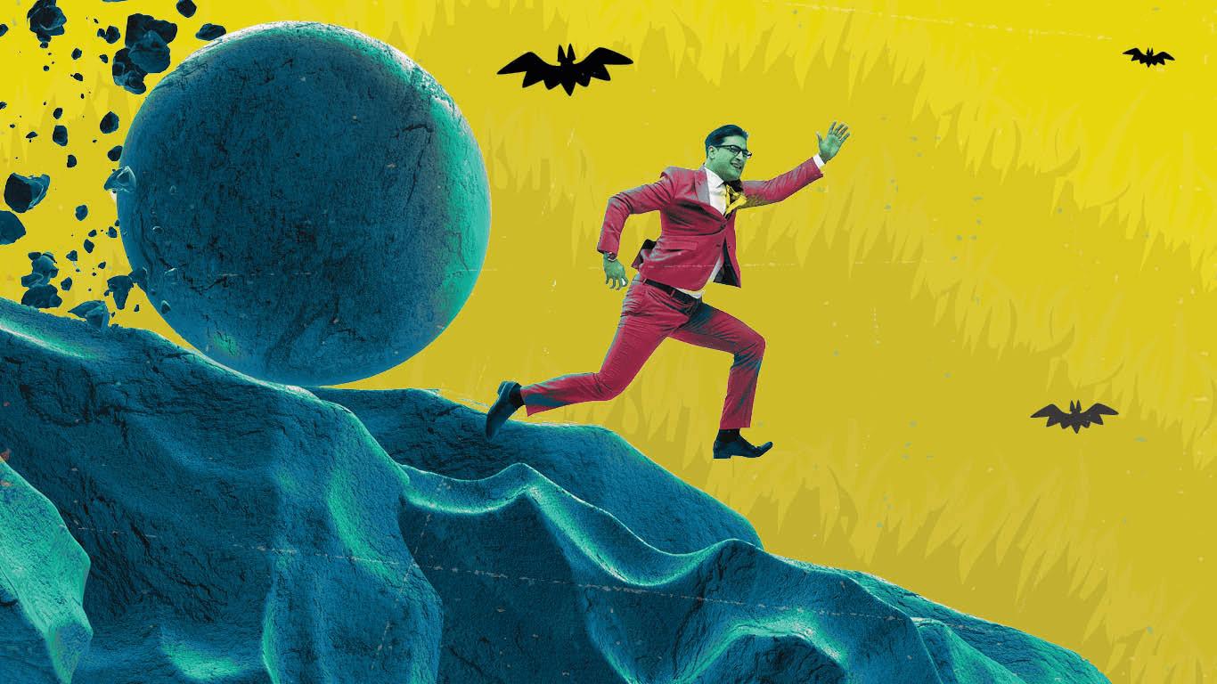 Businessman running downhill from boulder.