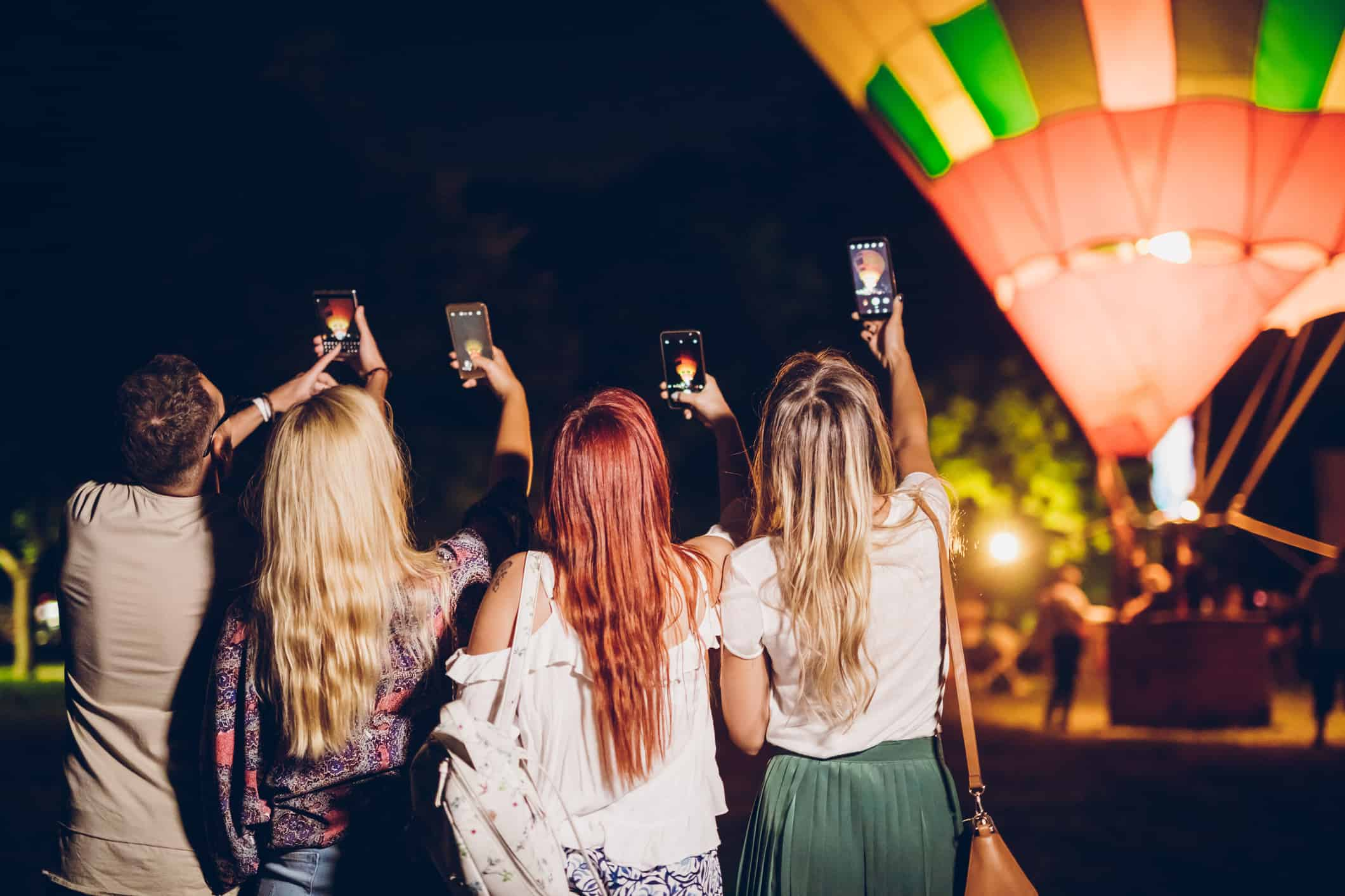 Group of friends taking pictures of a hot air balloon on a music festival.