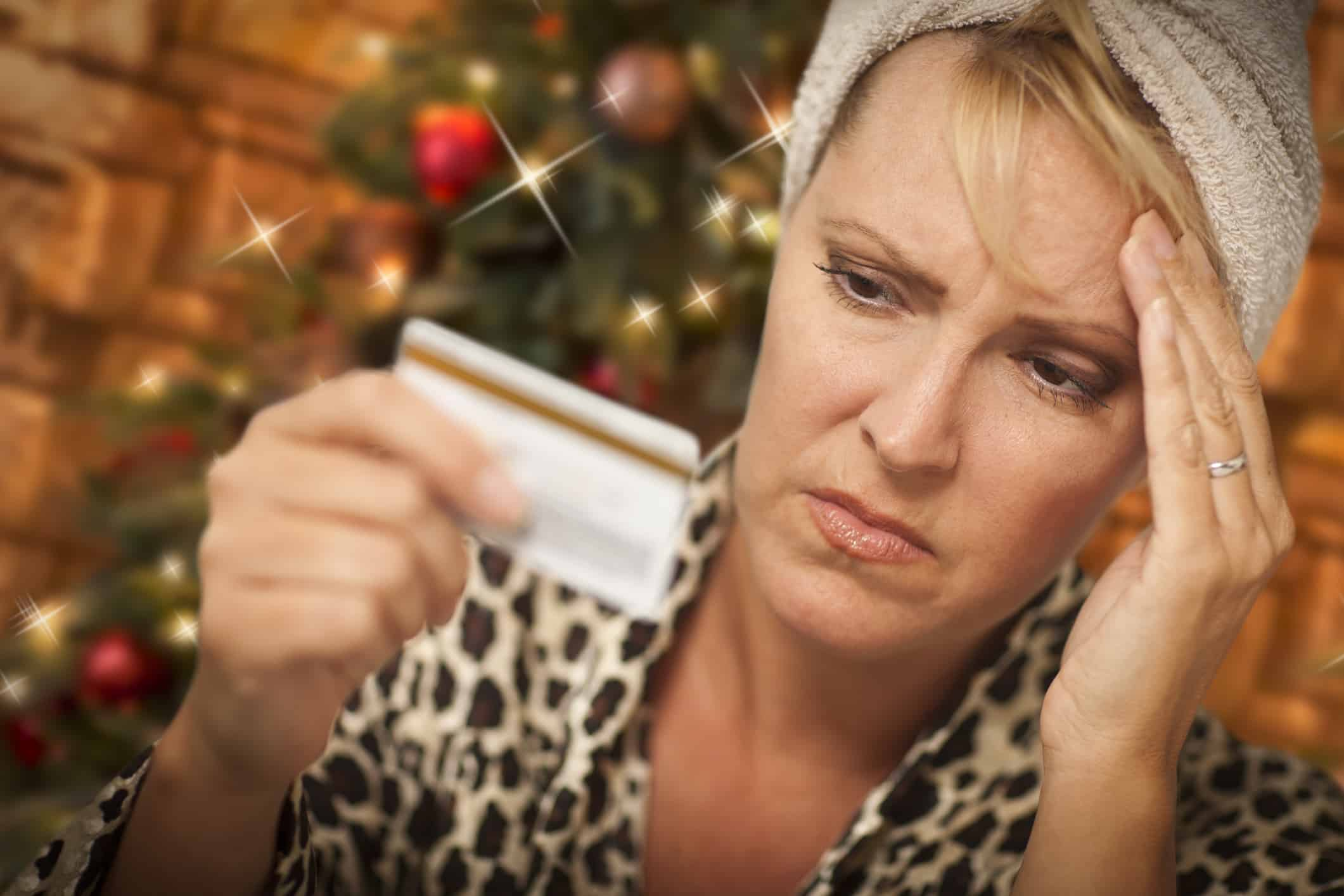 Very Upset Woman Holding Credit Card In Front of Christmas Tree.
