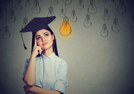 Graduate student young woman in cap gown looking up at bright light bulb.