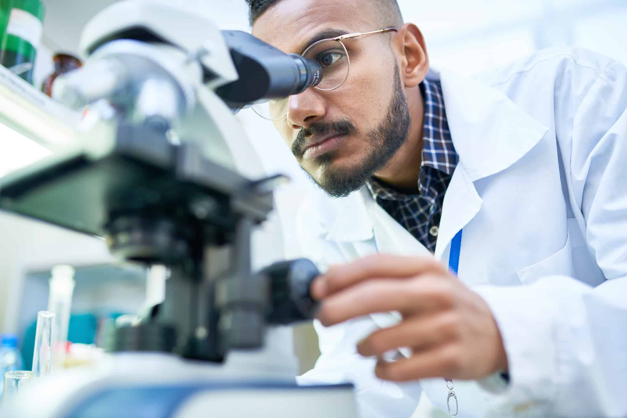 Portrait of young scientist looking in microscope while working on medical research in science laboratory.