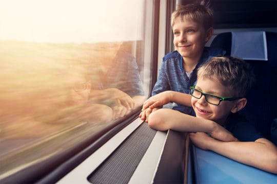 Tips for traveling with kids — Little brothers enjoying travelling by train.