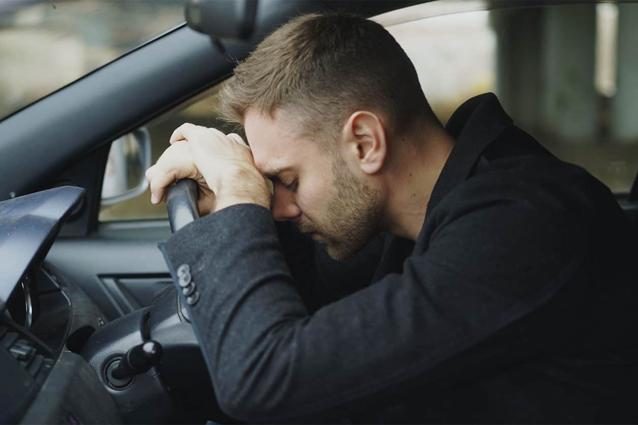 Young man sitting inside car is very upset and stressed
