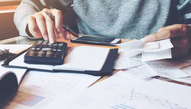 Man using calculator to check tax withholding in home office.