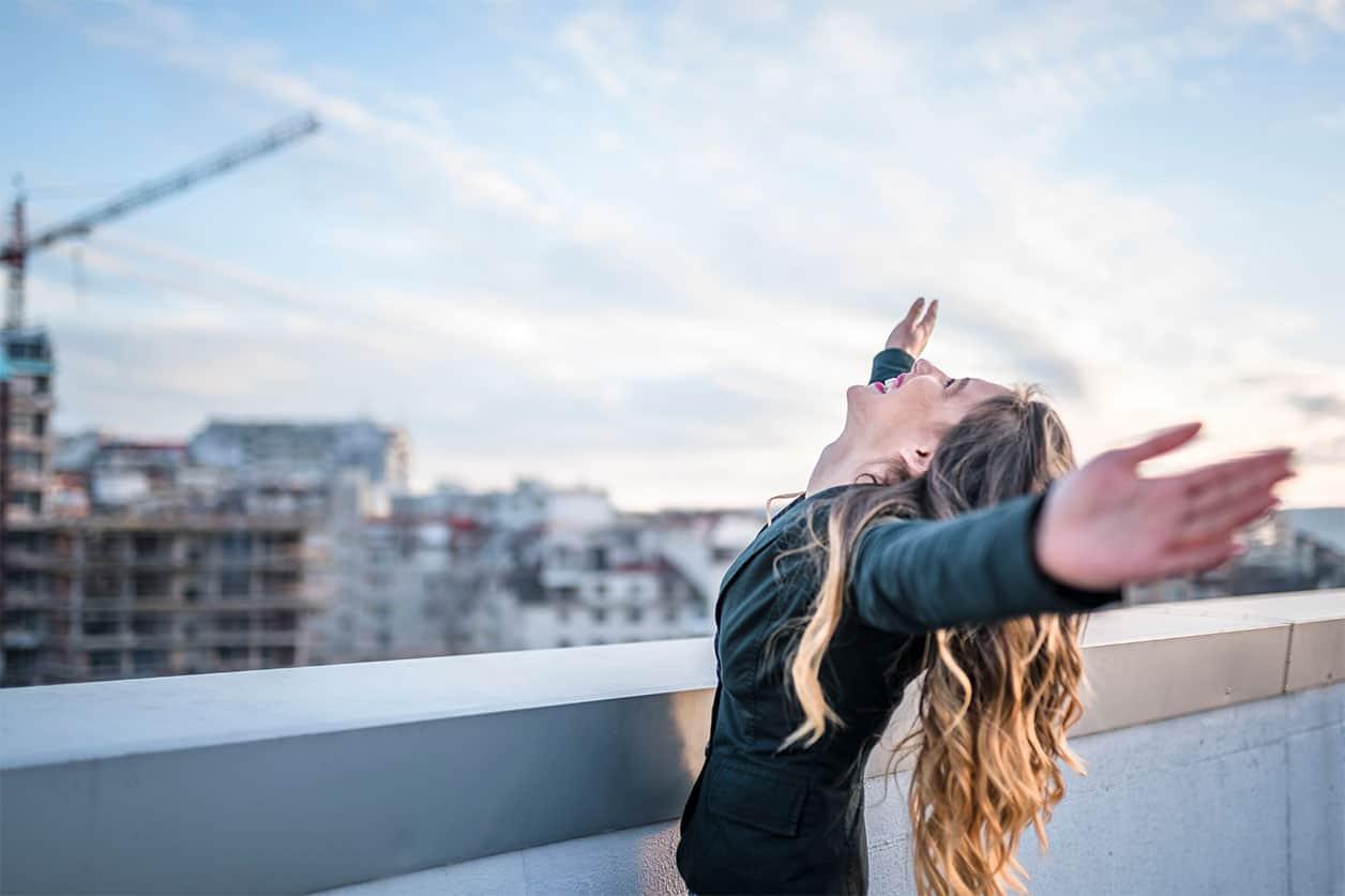 Businesswoman celebrating on urban rooftop