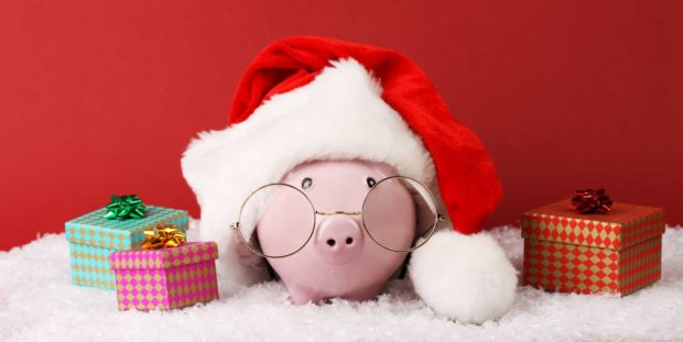 Black piggy box with text Xmas standing on white fur on red background