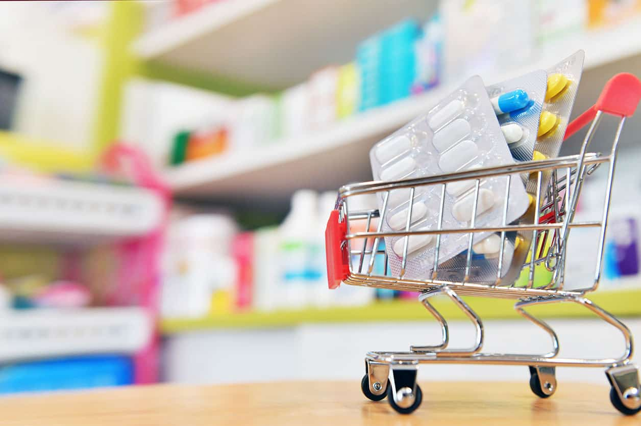Shopping cart filled with blister packs of medicine in drugstore