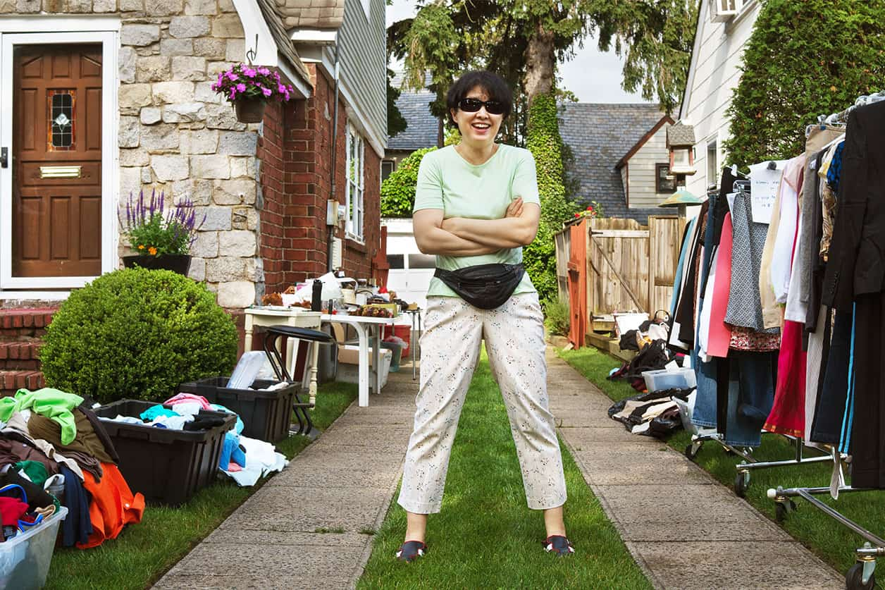 Happy woman ready to sell items at yard sale