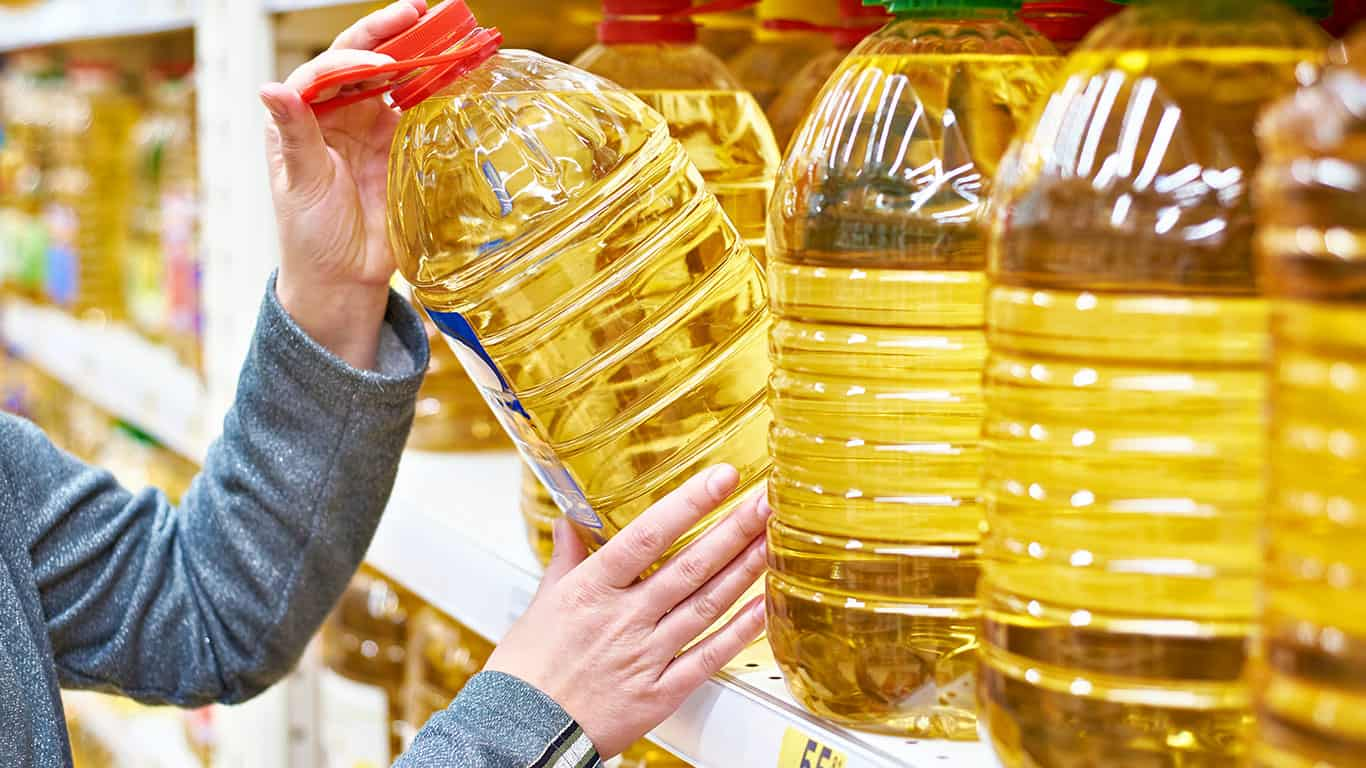 Big bottle of oil in hand buyer at grocery