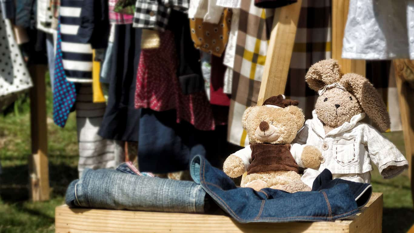 Handmade stuffed toys in wooden box at yard sale