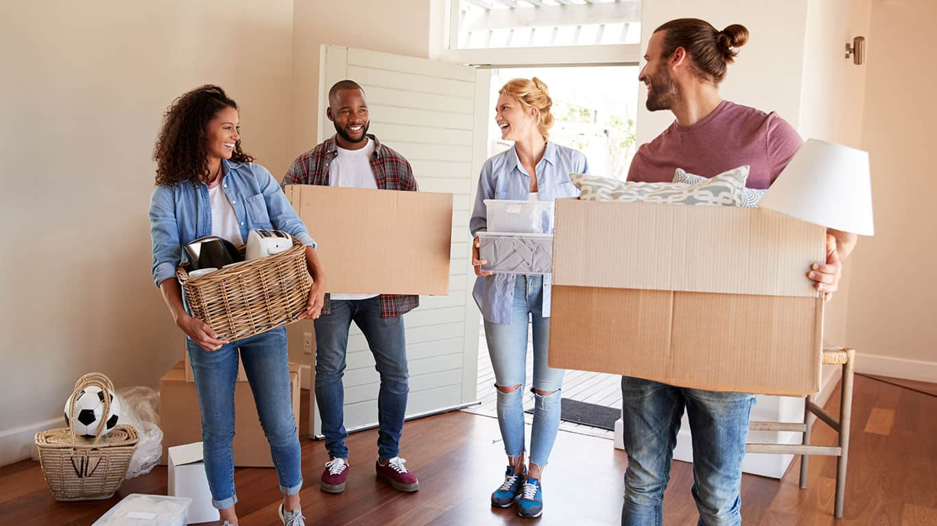 Friends Help Couple To Carry Boxes Into New Home On Moving Day