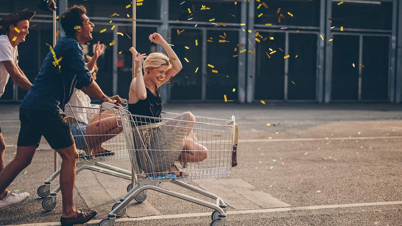Multiethnic young people racing with shopping cart and blowing confetti