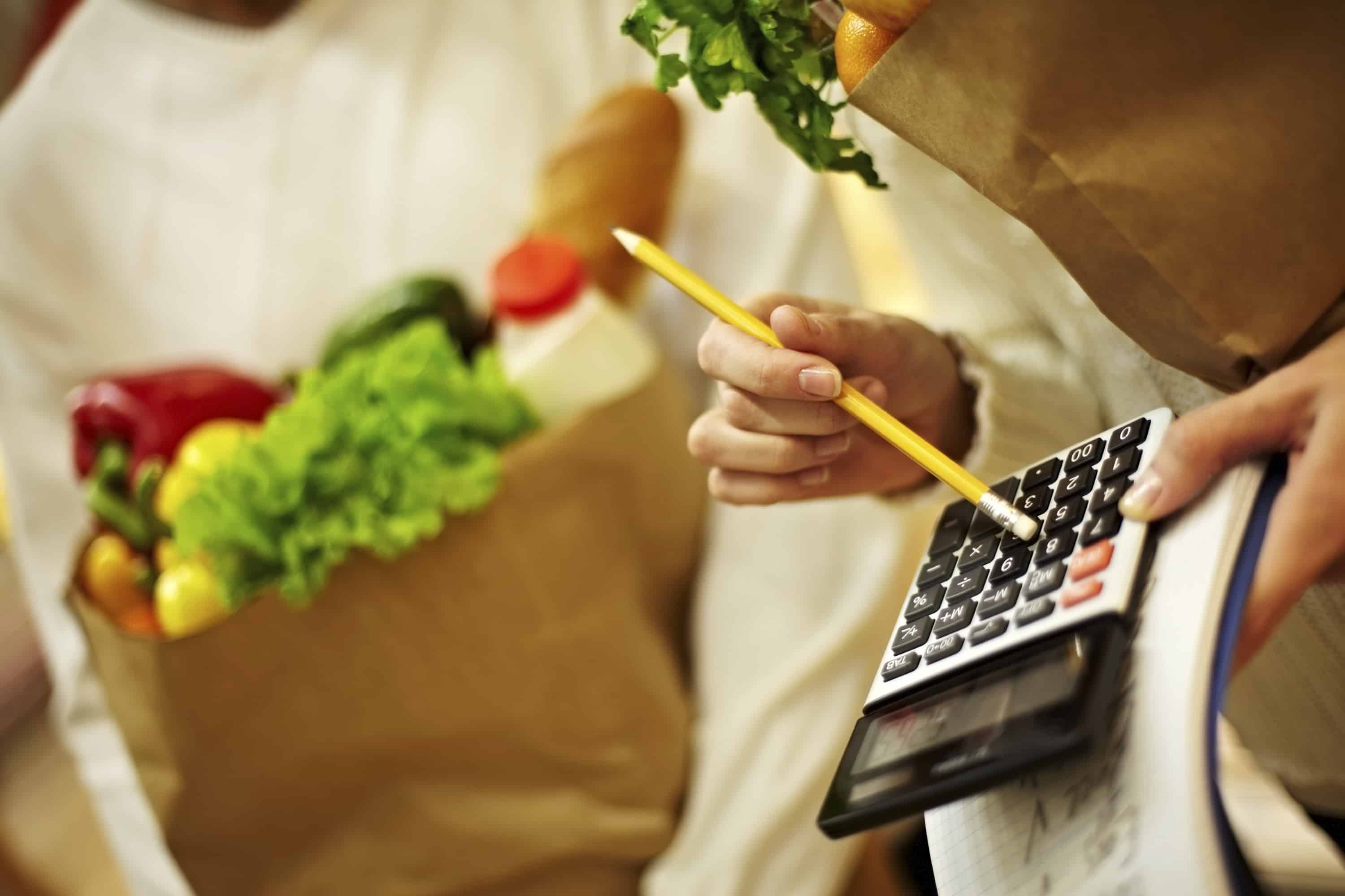 Woman counting expenses with calculator at supermarket, learning how to save money on food