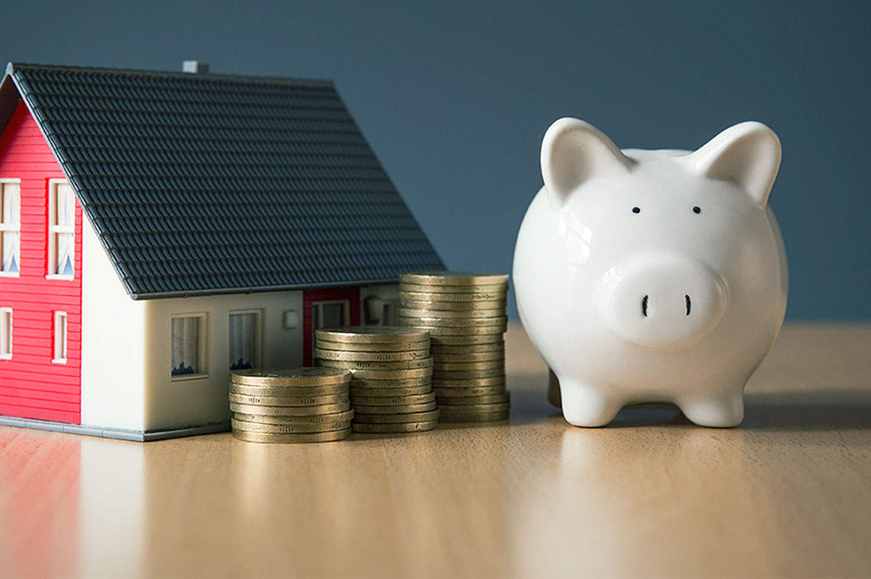 Saving money for house concept with white piggy bank