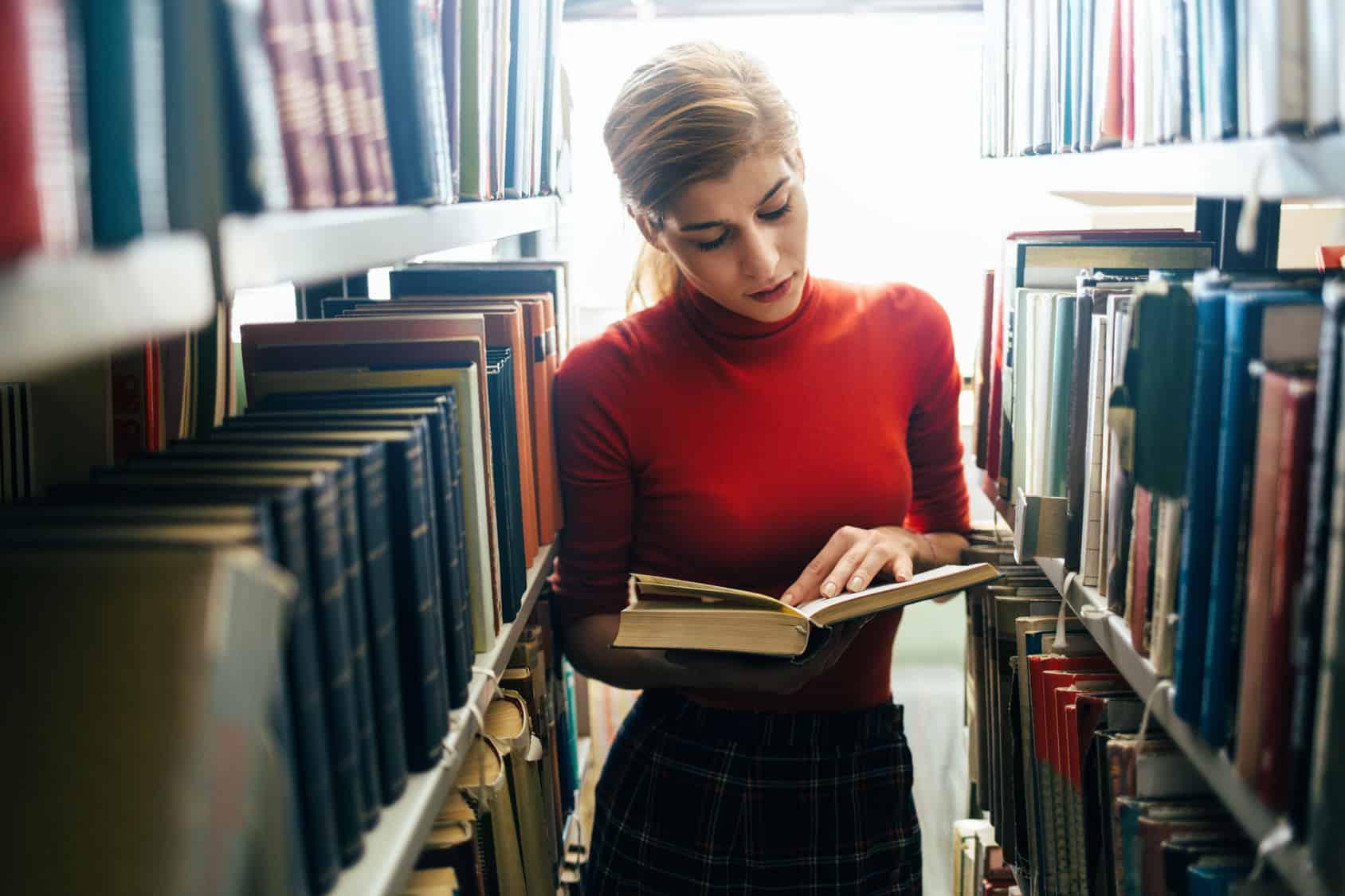 Mujer usando la biblioteca del campus universitaro