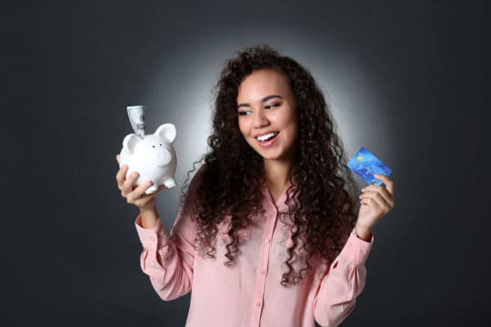Beautiful young girl holding piggy bank and credit card on grey background