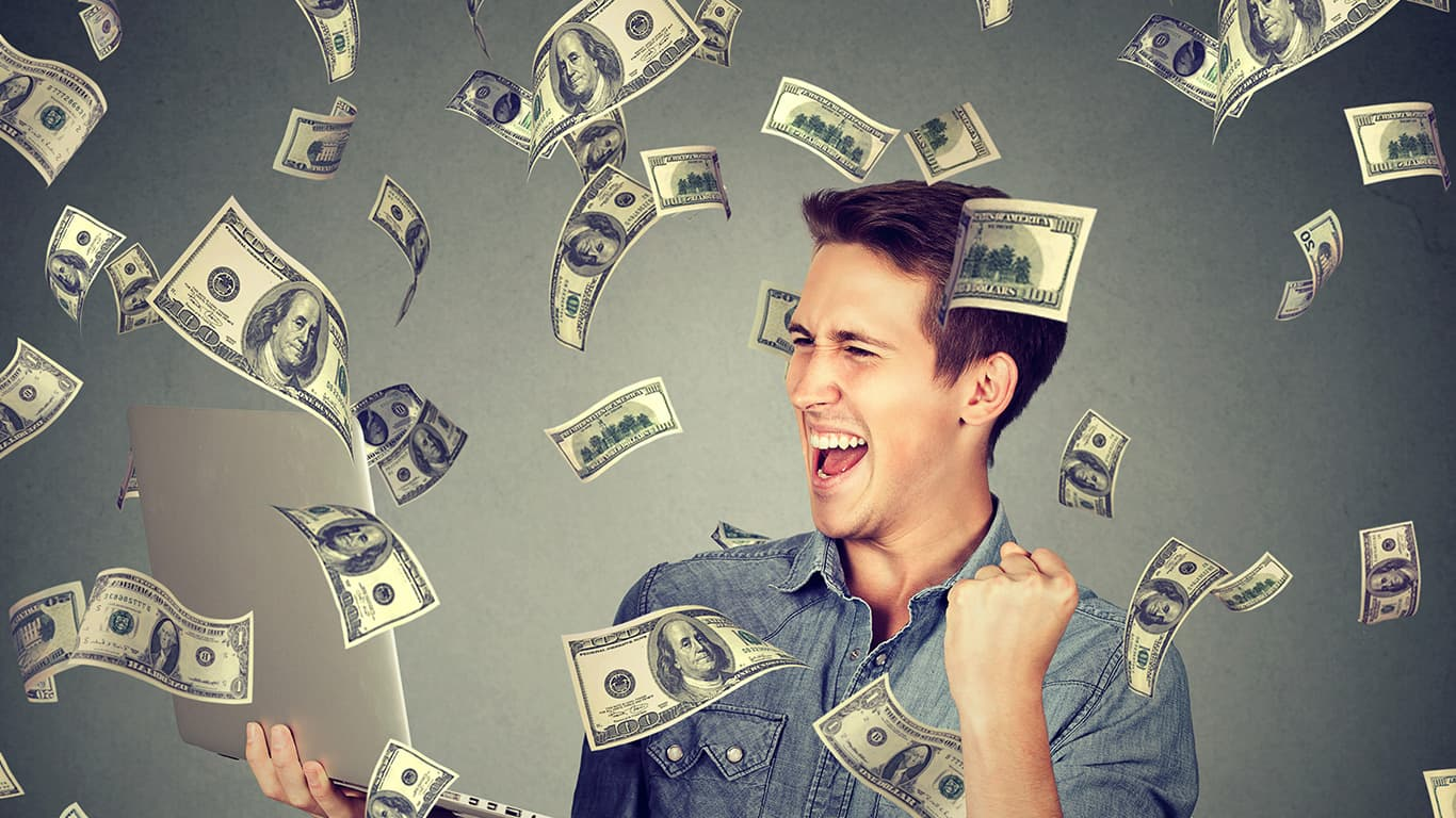 Successful young man using laptop building online business making money dollar bills cash falling down