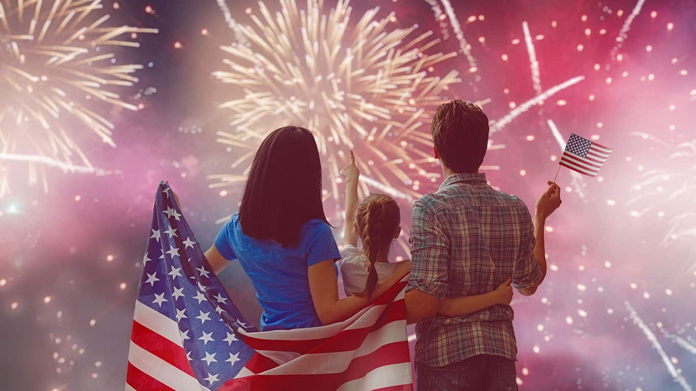 Happy family, parents and daughter child girl with American flag outdoors