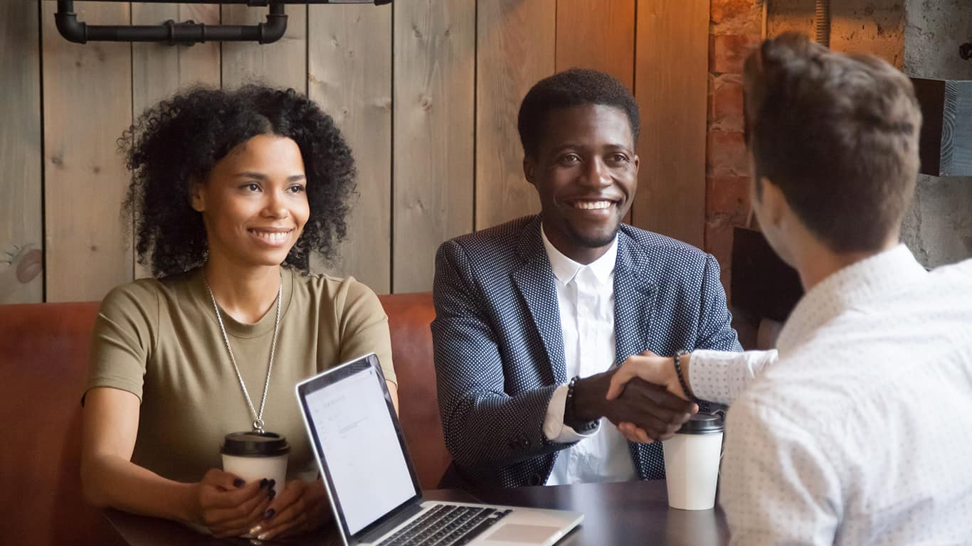 Smiling african american couple shaking hands to mortgage insurance broker