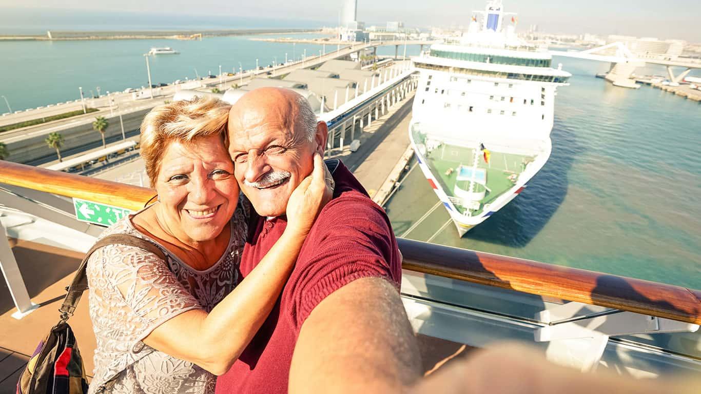 Senior happy couple taking selfie on ship on harbor background