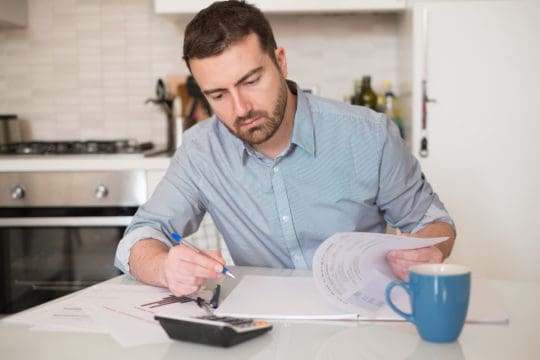 how to get a loan with bad credit; man working on improving his credit score with a calculator at a table