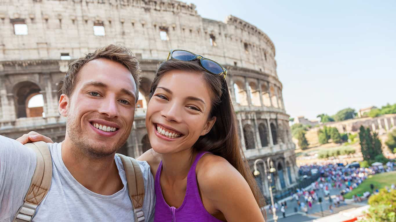 Travel selfie couple taking photo with phone at colosseum famous landmark in Rome city.