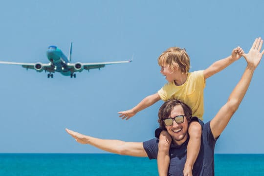travel insurance - father and son with plane in background