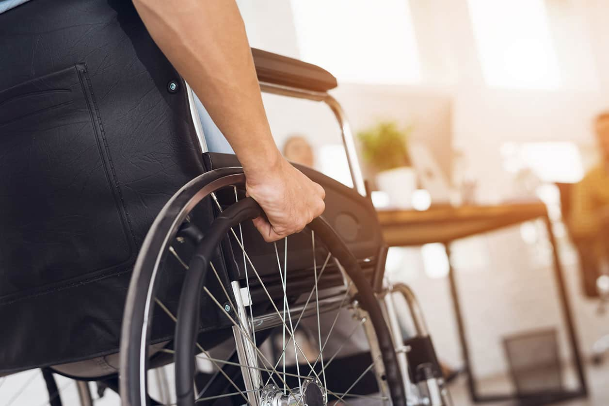 A disabled man is sitting in a wheelchair can student loans be forgiven if disabled