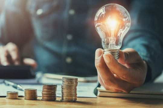 Business man hand holding lightbulb with using calculator to calculate and money stack