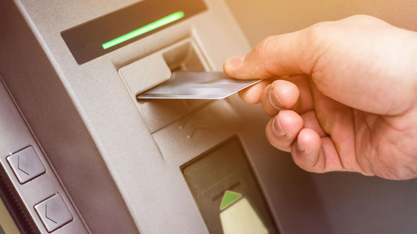 Hand of a man with a credit card, using an ATM